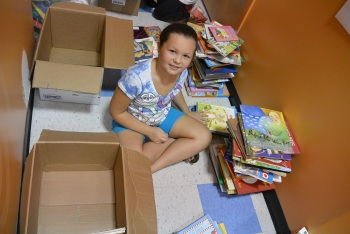 Charley volunteering her time to help sort books during our recent children's book drive.